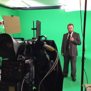 Ben McKenzie in suit and tie, performing in front of a green screen to camera